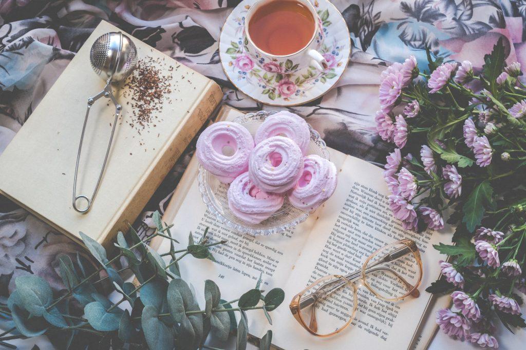 Mai multe obiecte langa un roman de dragoste pe un asternut floral