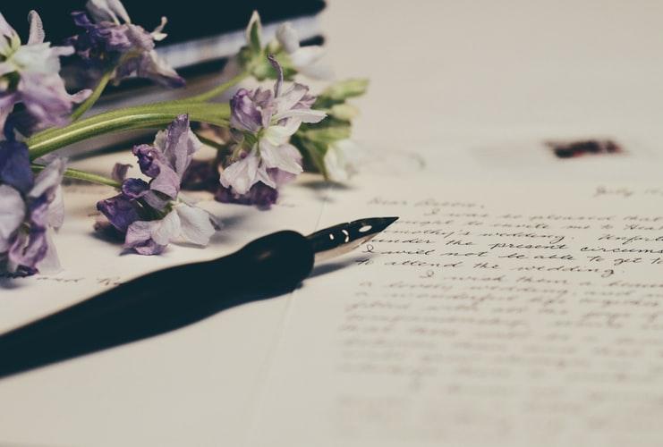 Masa pe care se afla flori, stilou si o scrisoare